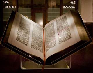 A large book, placed on a Plexiglas stand, lies open to a page containing elaborate type.