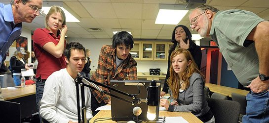 Five students and two educators sit and stand around a table to examine some scientific equipment.