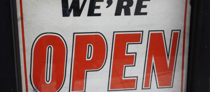 A sign hanging on a glass door that reads 'We're open'.